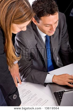 Business couple working on a laptop isolated over white