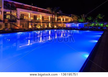 swimming pool with lighting in spa modern European hotel at night