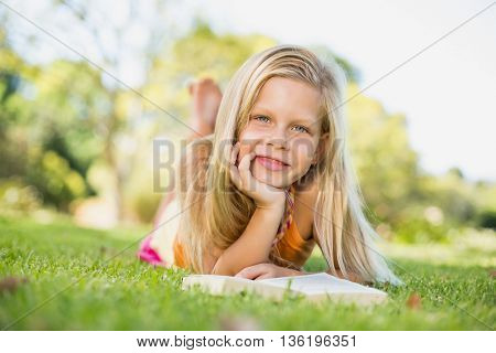 Portrait of young girl lying on grass with book in park