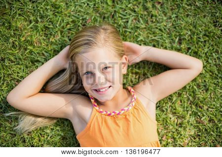 Portrait of cute young girl lying on grass in park