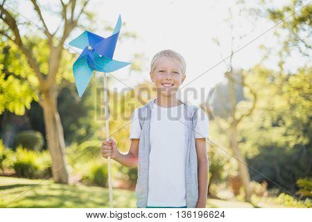 Portrait of boy holding a pinwheel in park