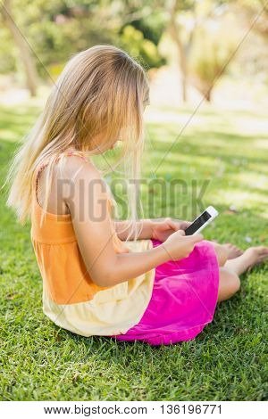 Young girl using mobile phone in park