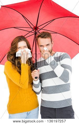 Young couple holding umbrella and wiping nose with a tissue on white background