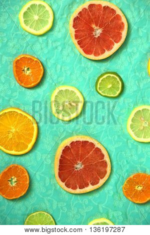 Fresh slices of citrus on a turquoise background