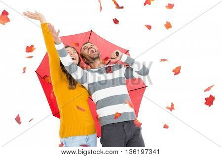 Young couple holding umbrella and playing with maple leaves on white background