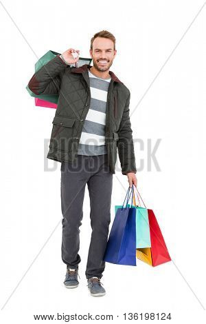 Young man holding shopping bags on white background
