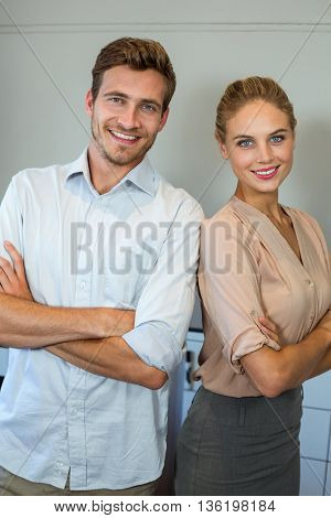 Portrait of happy man and woman standing against wall at office