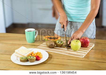 Midsection of young woman cutting fruits at kitchen counter