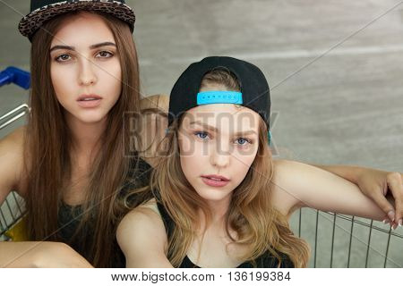 Portrait of beautiful blonde and brunette friends in caps looking at camera while sitting in shopping cart