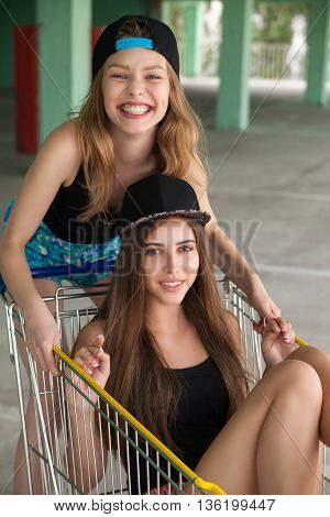 Portrait of jovial beautiful girls in shopping cart on parking lot looking at camera