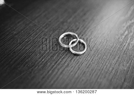 Black And White Photo Of Wedding Ring On Wooden Background