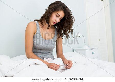 Young woman looking at medicine at bedroom