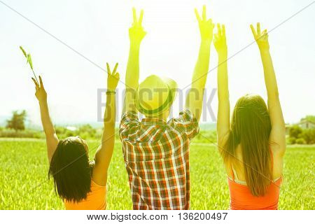 Multiracial friends putting hands up in countryside with back lighting - Multi ethnic young people enjoying sunny day outdoor in nature - Freedom in nature concept - Focus on hat - Vintage filter