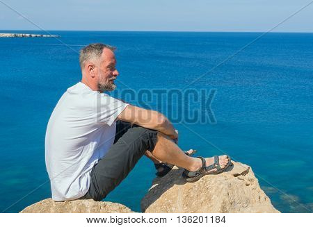 The bearded smiling man sitting on a rocky seashore and looks into the distance. Sunny day at sea.