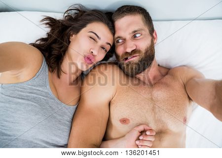 Couple making funny faces on bed at bedroom