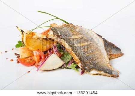 Fried white fish fillet with vegetable garnish