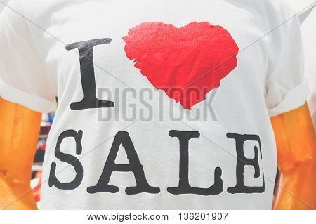Mannequin wearing sale t-shirt - Mall shop view during discount season time - Consumerism addiction concept - Warm filter with main focus on heart