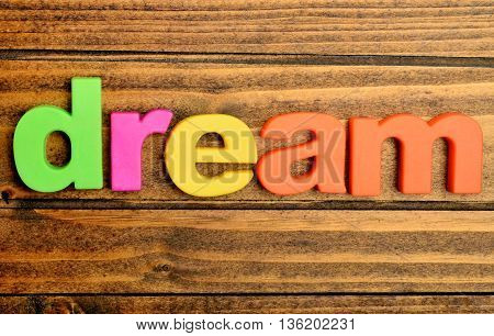 The word Dream on wooden table closeup