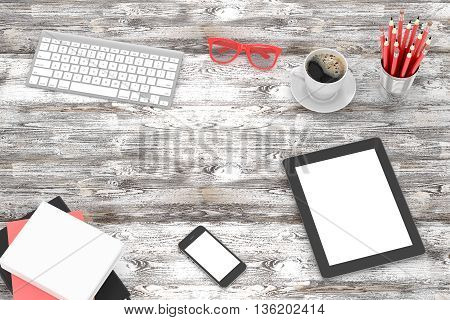Office workplace set on wooden grey table. Pc, tablet, smartphone, notebook, red stationery, red glasses, cup of coffee, keyboard.