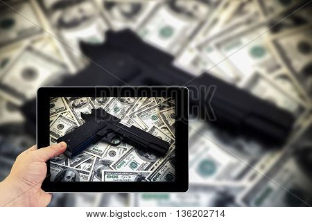 Tablet photography concept. Taking pictures on a tablet. Black and chrome gun pistol and money dollars background