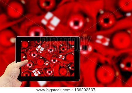 Tablet Photography Concept. Taking Pictures On A Tablet. Background Of Red Christmas Tree Balls, Lit