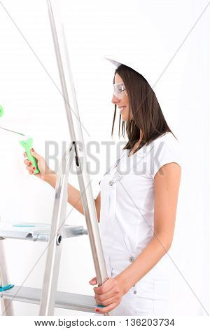A beautiful young adult woman painting a wall in her home in white.