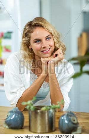 Happy young woman with hand on chin sitting at home