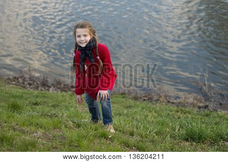 girl in red raincoat and blue jeans on the of river shore