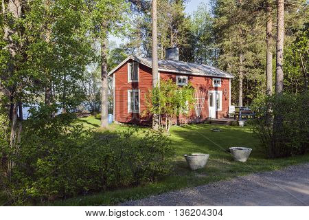 UMEA, SWEDEN ON MAY 28. View of a wooden Falu Red Painted cabin by a lake on May 28, 2013 in Umea, Sweden. Entry, garden and a grove of trees. Editorial use.