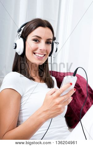 Portrait of a beautiful young woman in headphones listening to music with her smarthphone