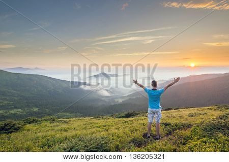 Hiker standing on top of a mountain with raised hands and enjoying sunrise
