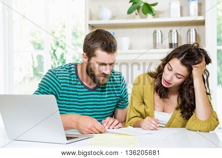 Couple checking their bills in kitchen at home
