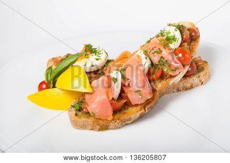 Italian sandwich bruschetta with salmon on white plate