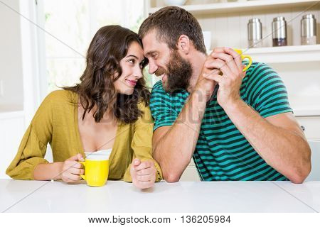 Couple having coffee in kitchen at home