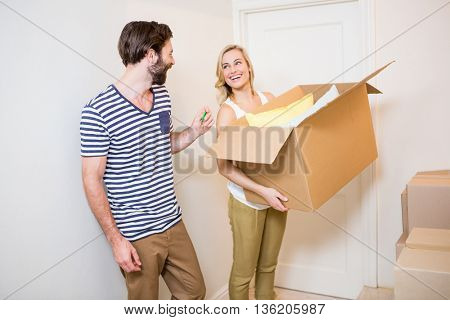 Happy couple holding a carton in their new house