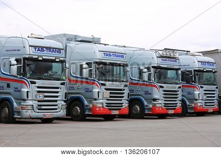 FORSSA, FINLAND - JUNE 24, 2016: Fleet of light blue Scania R truck tractors parked on asphalt yard