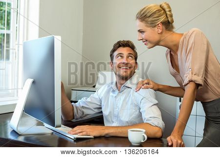 Happy colleagues discussing while working on computer at office