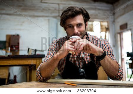 Carpenter is posing with his craft and his coffee in a dusty workshop