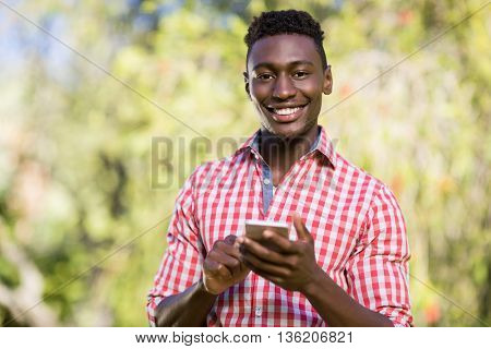Happy man posing and holding his smartphone at park