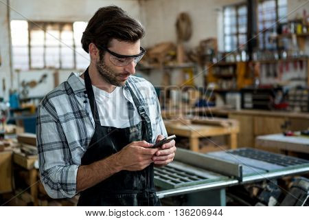 Carpenter texting someone and wearing protective glasses in a dusty workshop