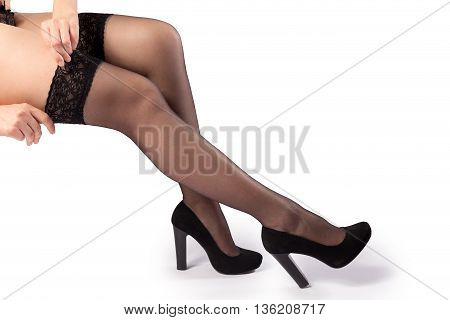 Woman putting on black stockings and high heels isolated on the white background