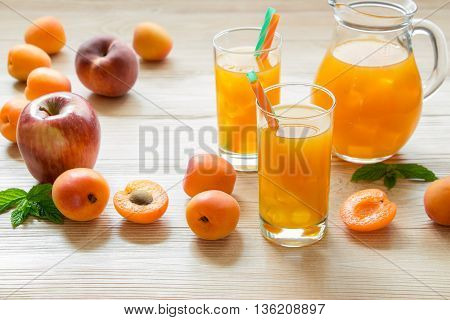 Right apricot peach apple juice in glasses with ice near the jar of juice and scattered apricots peaches apple left empty space on light wooden background. Apricot peach apple juice with ice.