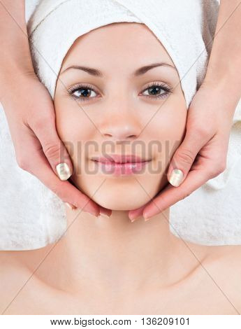 beautiful young woman enjoying facial massage procedure in spa