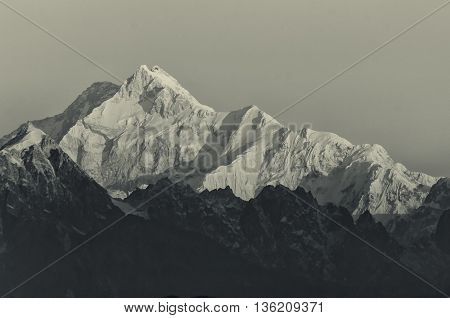 Beautiful first light from sunrise on Mount Kanchenjugha Himalayan mountain range Sikkim India. Tinted stock image.