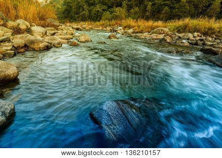 Beautiful Reshi River water flowing on rocks at dawn Sikkim India - a spectacular view tinted stock image
