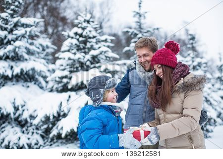 Happy family with present outdoors