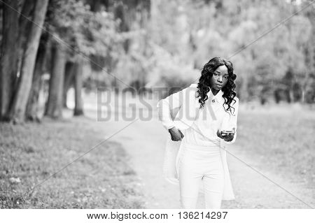 Stylish Black African American Girl Walking On Park With Mobile Phone At Hand