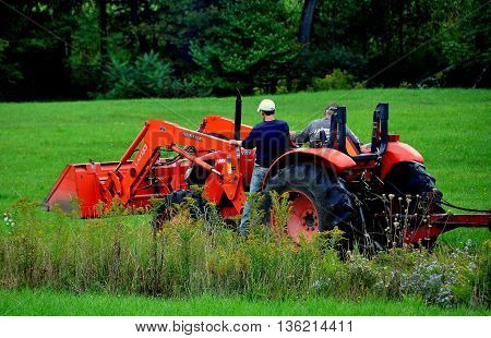 Conway Massachusetts - September 20 2014: Farmers on a large orange tractor driving through a grassy field on their farm