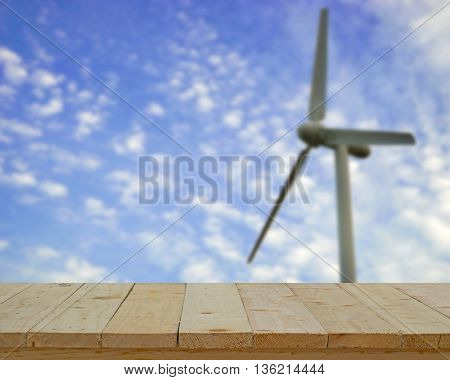 wood table top on blur background of single white turbine on blue sky - can use to display or montage on product