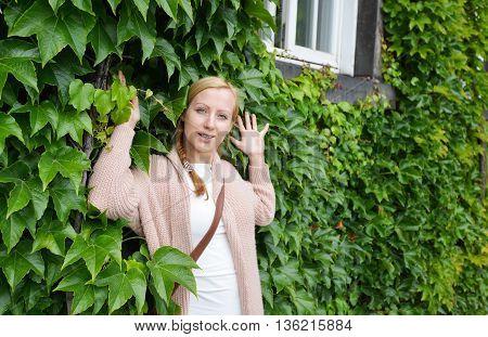 pretty woman on sidewalk alongside green ivy